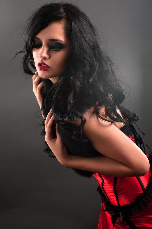 Sexy brunette in rood korsetbont en lang haar in s royalty-vrije stock afbeeldingen
