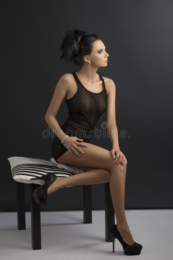 Download Brunette Is Sitting On Pillows, Looks At Left Stock Photo - Image: 26577340