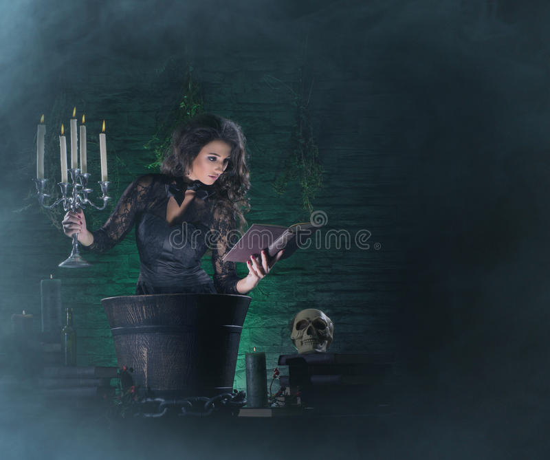 A brunette witch making poison in the dungeon stock photos