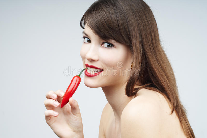 brunette woman biting a chili pepper stock images