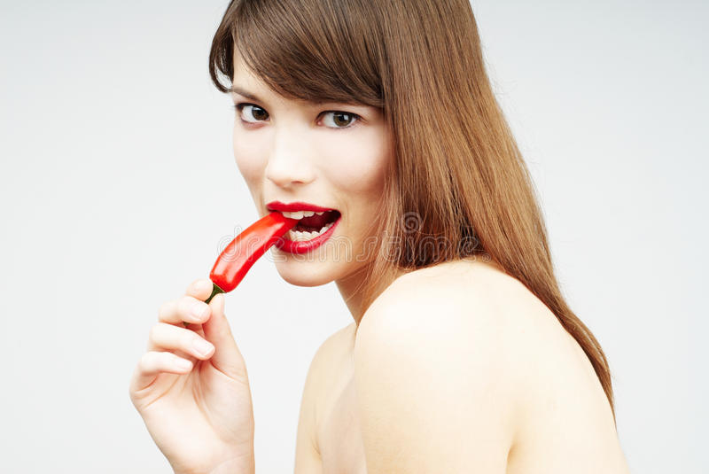 Download Brunette Woman Biting A Chili Pepper Stock Image - Image: 14850841