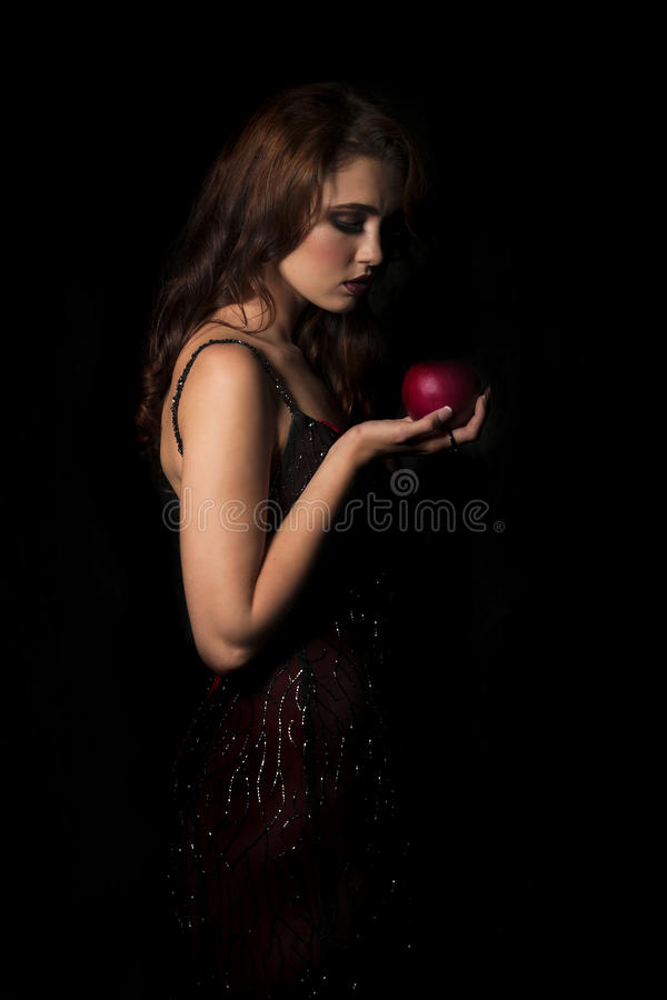 brunette woman with dark red dress looking down at red apple in her hand royalty free stock image