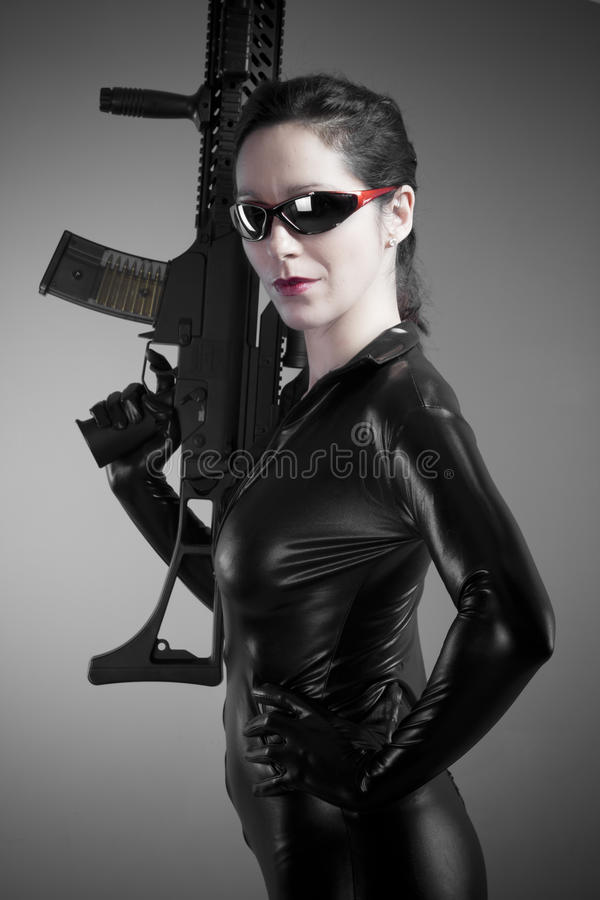 Brunette woman in latex jumpsuit with heavy gun and glasses. Art royalty free stock photography