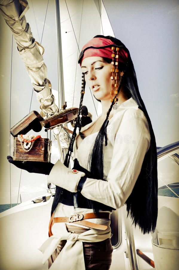 Brunette woman pirate. With a gun opens the treasure chest royalty free stock image