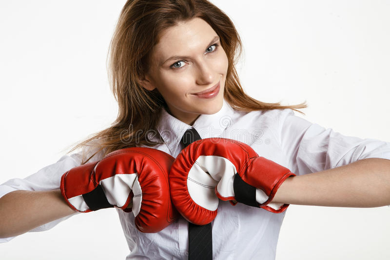 Brunette woman is ready to fight. Attractive woman in a white shirt with red boxing gloves on a white background stock photos