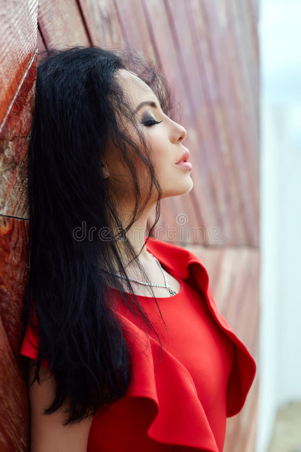 Brunette woman in a red dress is standing near the red gate. The wind blows the hair, romantic, delicate look, look, beautiful eyes. Girl resting in summer royalty free stock photography