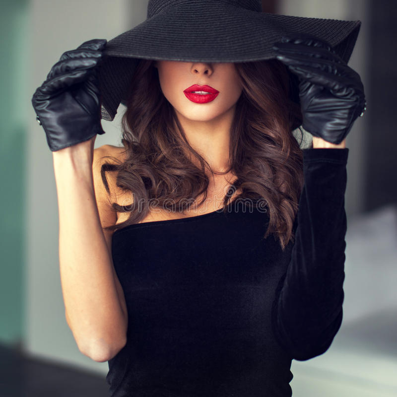 brunette woman with red lips in hat stock images