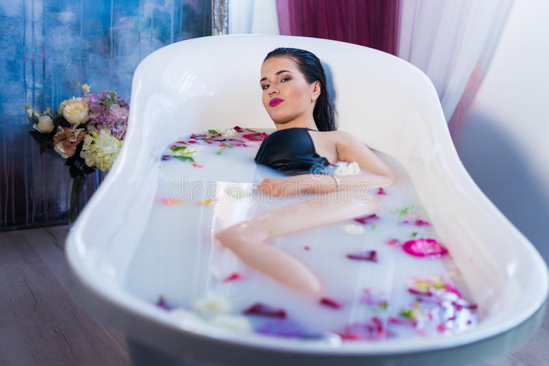 Brunette woman relaxing in hot milk bath with flowers. She is wearing black sexual lingerie and looking at camera stock images