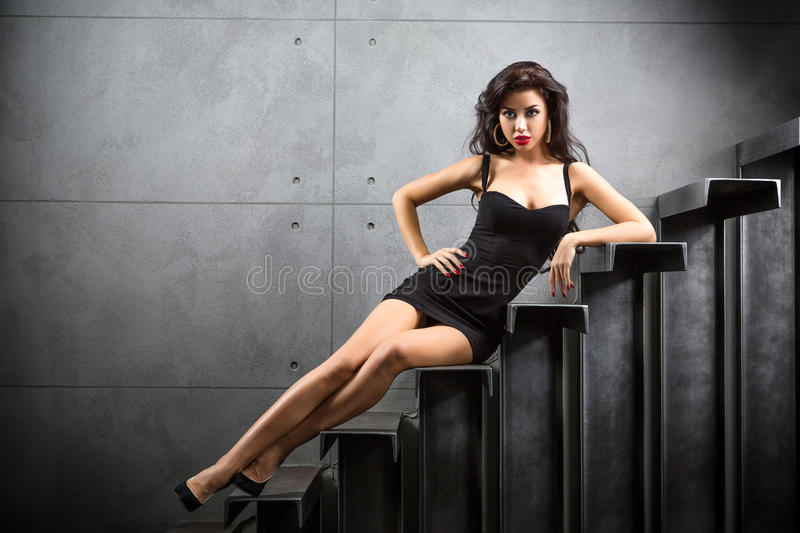 Brunette woman sitting on stairs. Woman lying on stairs at backyard of building royalty free stock photos