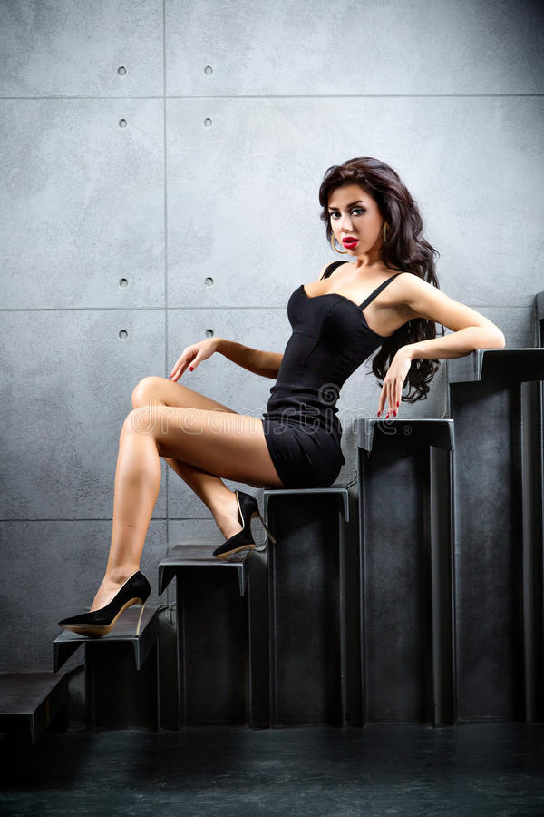Brunette woman sitting on stairs. Woman lying on stairs at backyard of building royalty free stock image