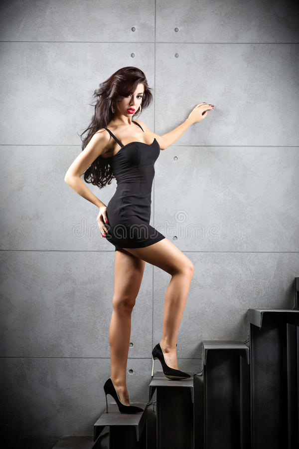 Brunette woman staying on stairs. Woman staying on stairs at backyard of building royalty free stock photography