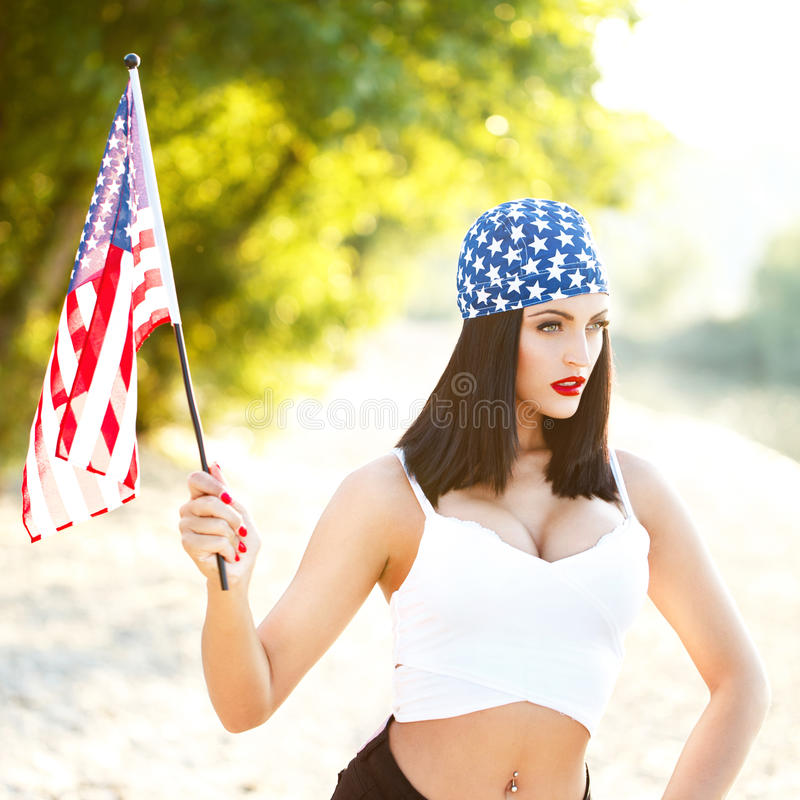 Brunette woman wih USA flag outdoor. Brunette woman with usa headscarf and flag outdoor portrait. Star spangled banner, independence day, 4th july royalty free stock image