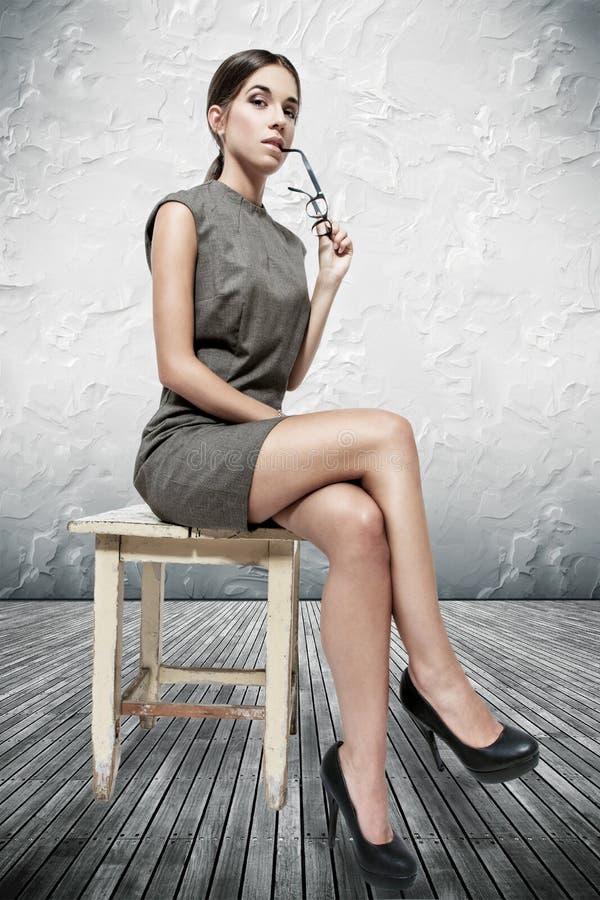 Sexy Brunettefrau, die auf Schemel sitzt stockfotografie