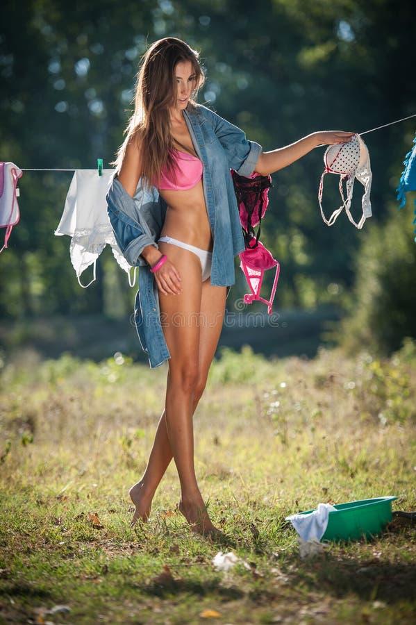 Sexy Brunettefrau im Bikini und in Hemd, die Kleidung setzen, um in der Sonne zu trocknen Sinnliche junge Frau mit den langen Bei lizenzfreie stockfotos