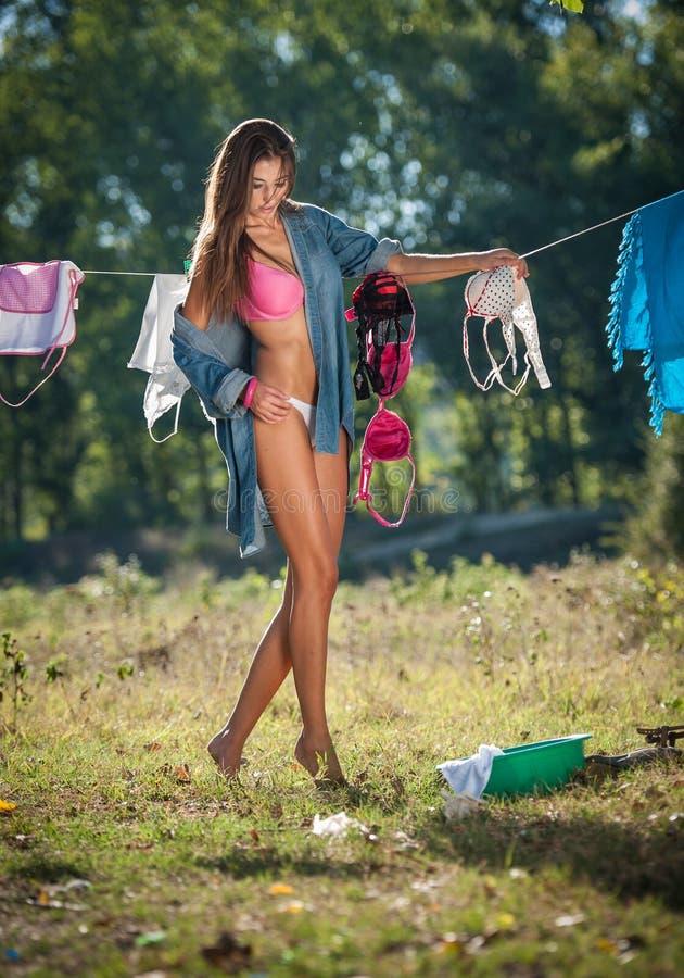 Sexy Brunettefrau im Bikini und in Hemd, die Kleidung setzen, um in der Sonne zu trocknen Sinnliche junge Frau mit den langen Bei stockfotografie