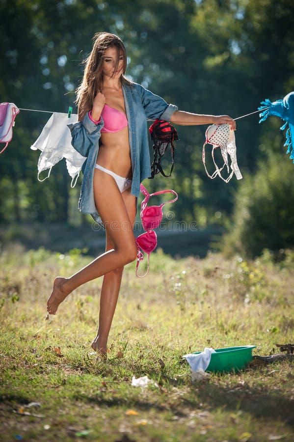 Sexy Brunettefrau im Bikini und in Hemd, die Kleidung setzen, um in der Sonne zu trocknen Sinnliche junge Frau mit den langen Bei stockbilder
