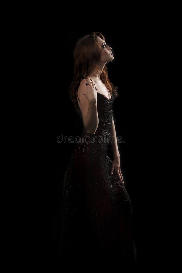 Sexy Brunettefrau mit dunkelrotem funkelndem Abendkleid stockfotos