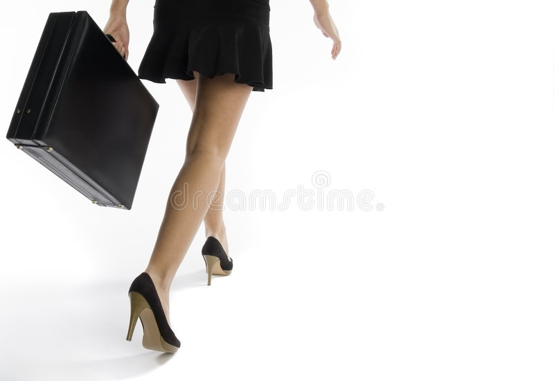 Business woman. Low angle view of business woman walking with briefcase royalty free stock images