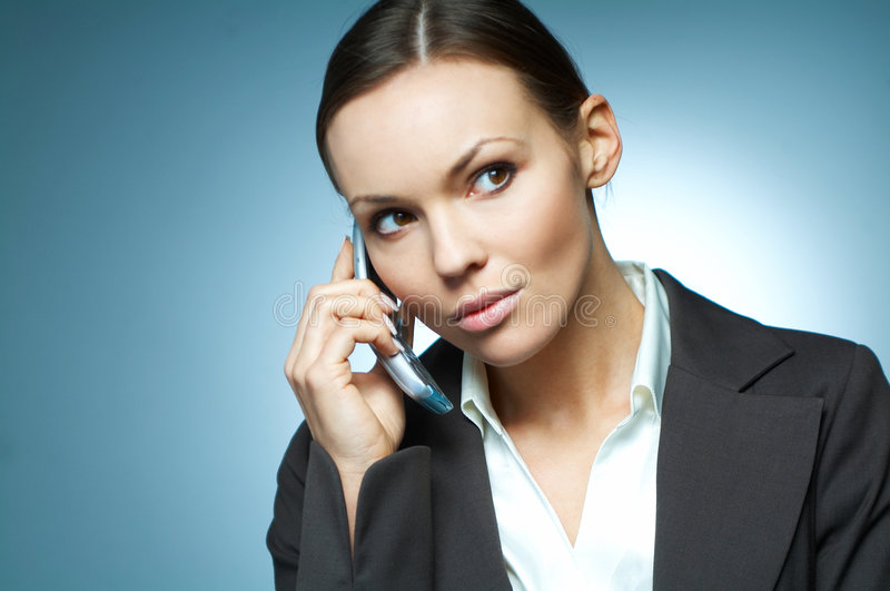 Business Woman MG. Beautiful and brunette business woman isolated on clear background is using mobile phone royalty free stock image