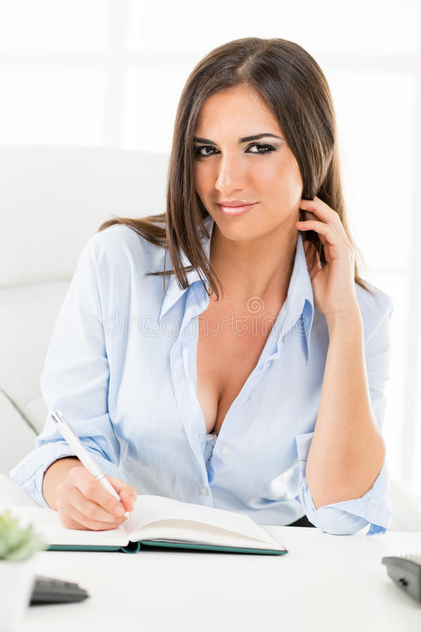 Businesswoman With Cleavage. A young pretty businesswoman with cleavage sitting at a table, writing in planner and seductively looking at the camera stock photos