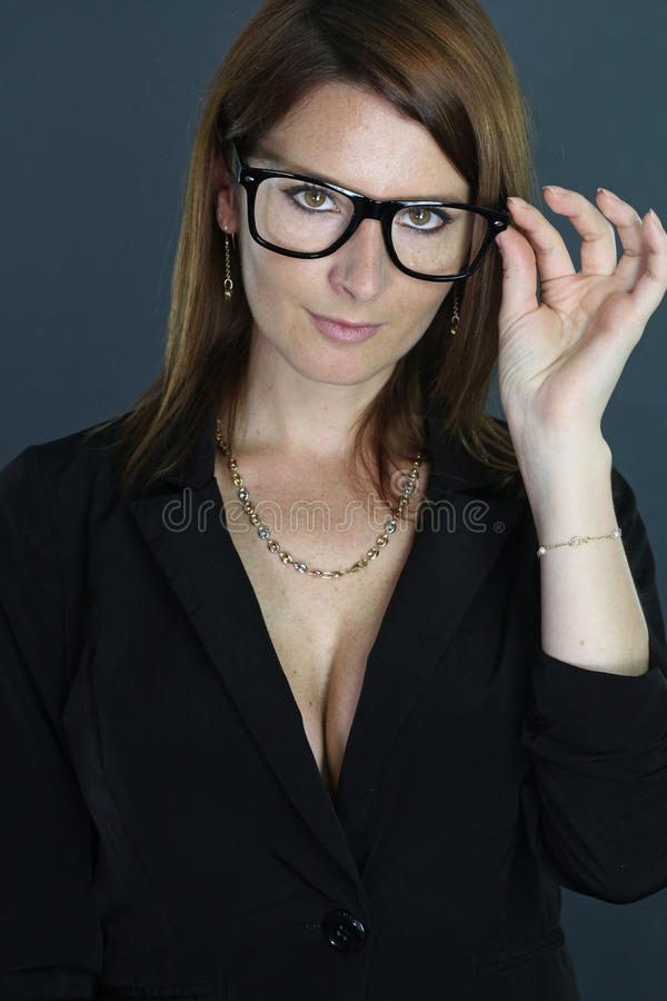 Businesswoman holding her glasses. Businesswoman posing over a gray background stock image