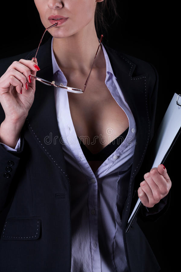 Businesswoman with unbuttoned shirt. Holding glasses royalty free stock image