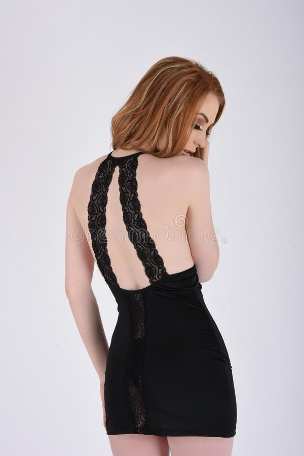 Sexy, Busty Redhead in a Short, Tight Black Lace Party Dress. Beautiful, tall, slim, busty redhead model dressed in a short, sexy, tight, black, lace party dress stock image