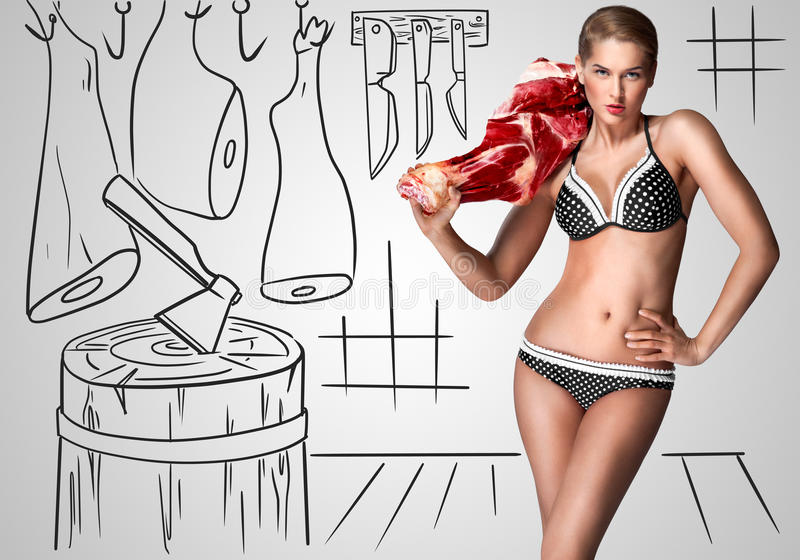 Butcher. Creative portrait of a beautiful female butcher in bikini holding raw meat on her shoulder on sketchy background of a butcher shop royalty free stock photography