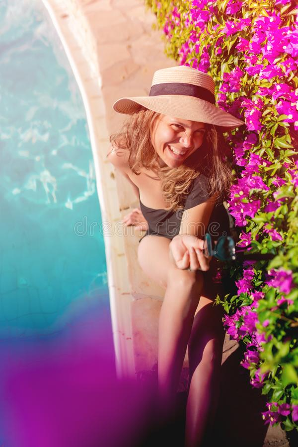 caucasian woman smiling at swimming pool, poolside with straw hat and sunglasses stock photos