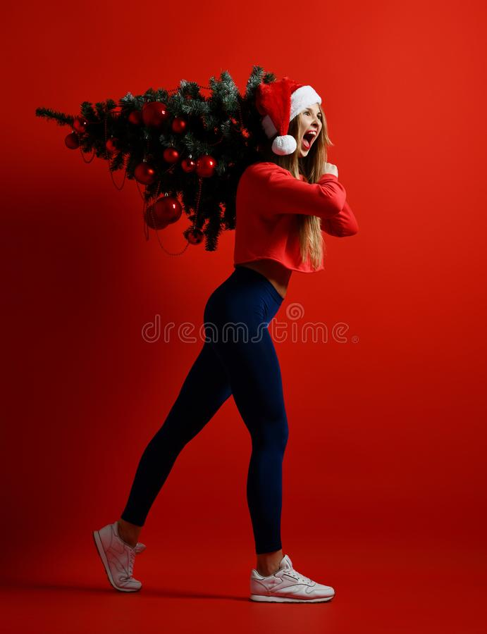 Christmas fitness sport woman wearing santa hat holding xmas tree on her shoulders. Running forward on a red background stock photos
