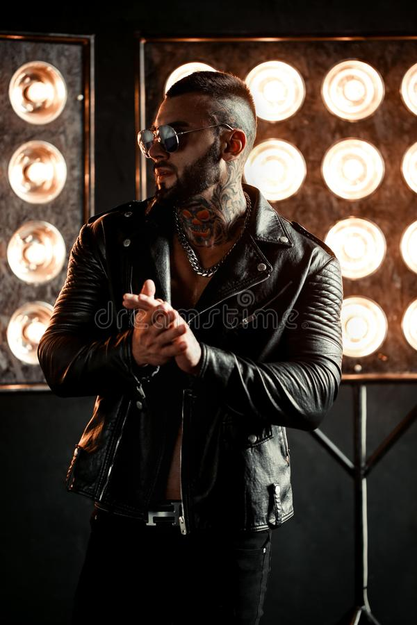 closeup portrait of brutal handsome male model in fashion leather jacket and with a black beard. Tattoo skull and stock images