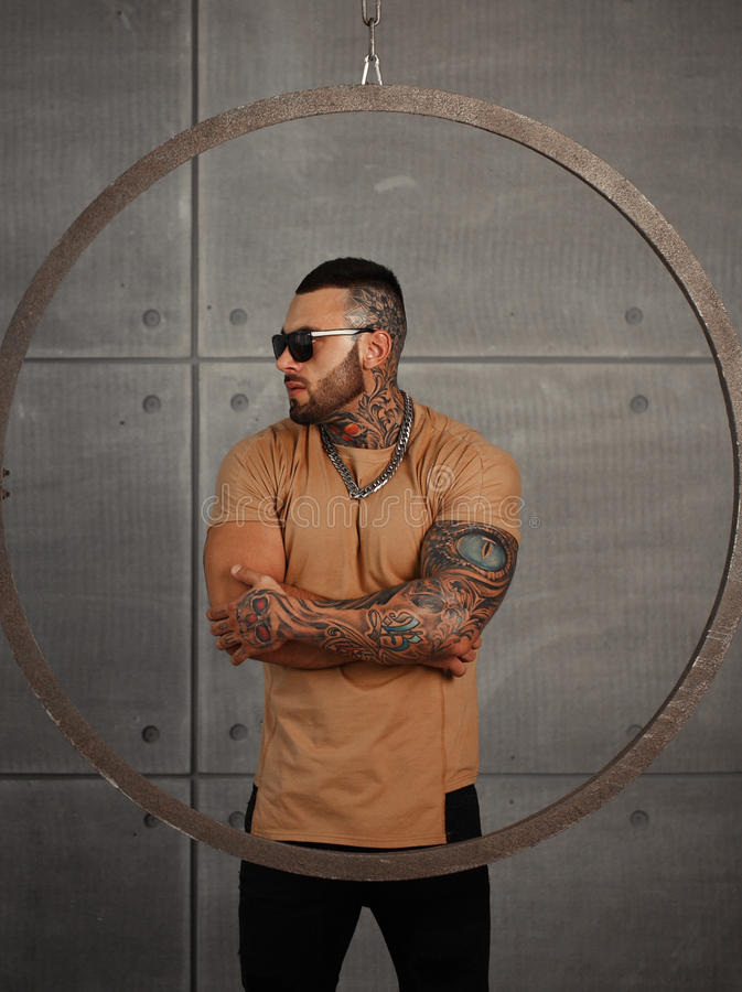 closeup portrait of Elegant handsome male model with fashion tattoo and a black beard standing and posing for model royalty free stock images