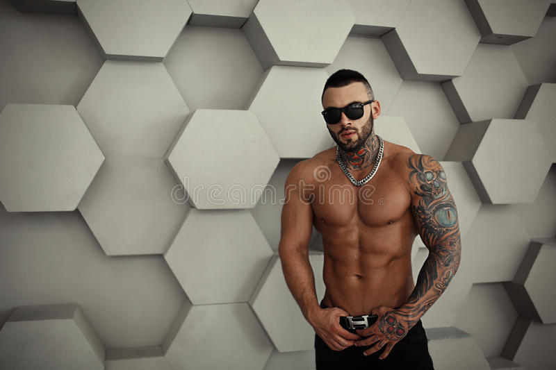 Closeup topless portrait of Elegant handsome male model with fashion tattoo and a black beard standing and posing. For tests or to journal in trend fashionable royalty free stock photography