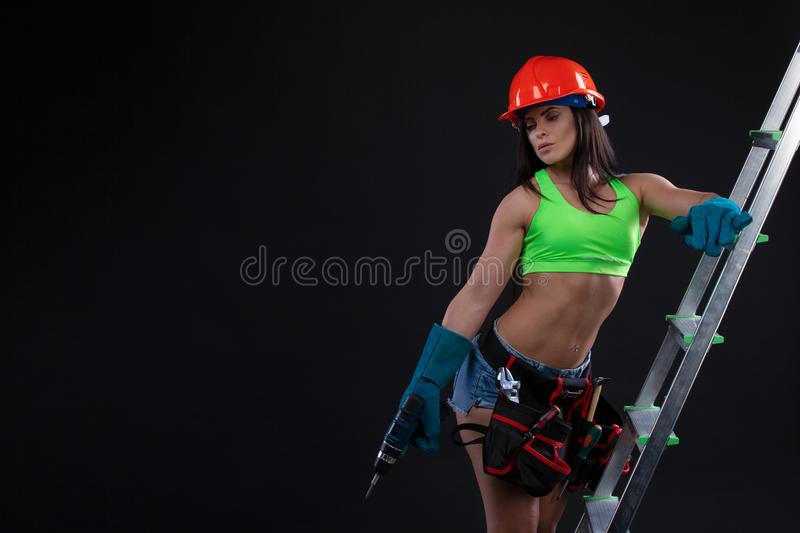 construction female worker with drill and ladder on black background stock photos