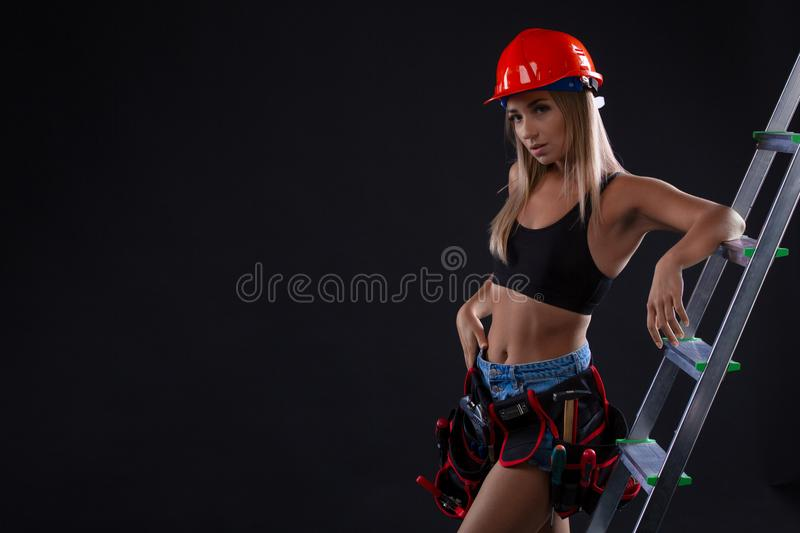 construction female worker with ladder on black background. woman is wearing a construction helmet and a belt with tools stock photography