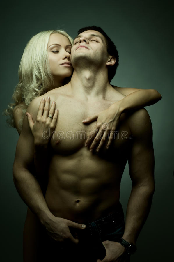 Couple. Muscular handsome guy with pretty woman, on dark background, glamour green light