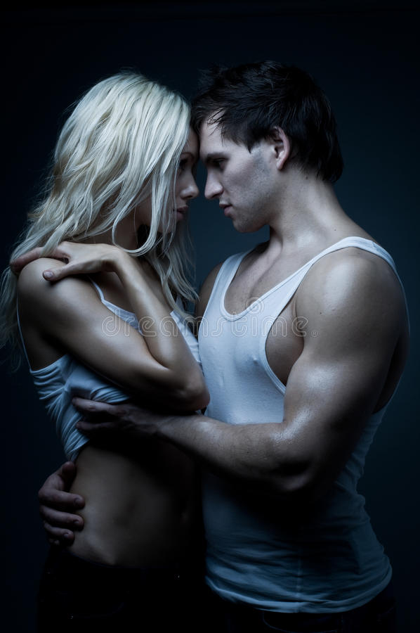 Couple. Muscular handsome guy with pretty woman, on dark background, glamour blue light