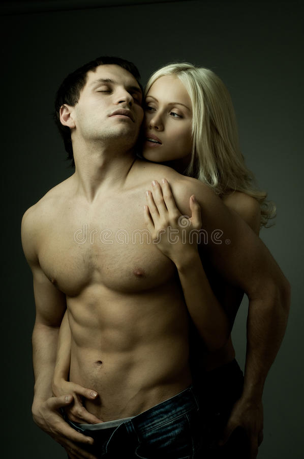 Couple. Muscular handsome guy with pretty woman, on dark background, glamour light
