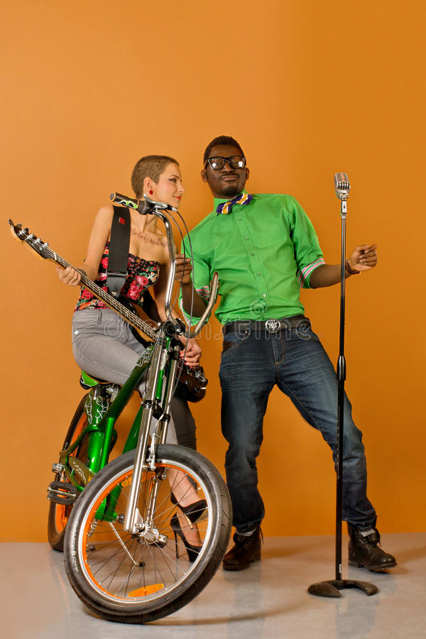Download Couple In Front Of A Bycicle On Orange Background Stock Photo - Image: 41056636
