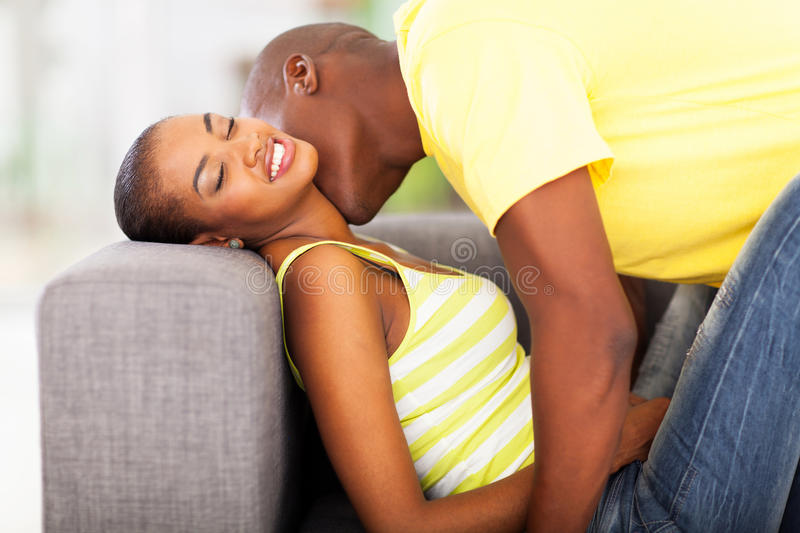 Couple kissing. Young african american couple kissing on the sofa royalty free stock photos