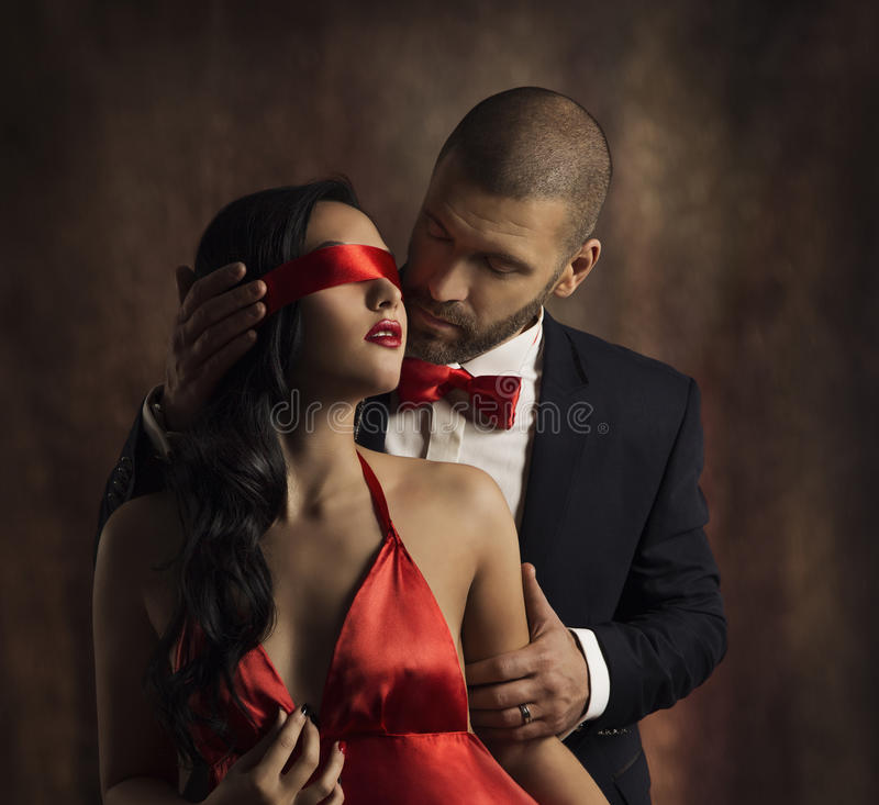 Couple Love Kiss, Man Kissing Sensual Woman in Blindfold. Couple Love Kiss, Man in Suit Kissing Sensual Woman, Red Fashion Blindfold on Girl Eyes stock images