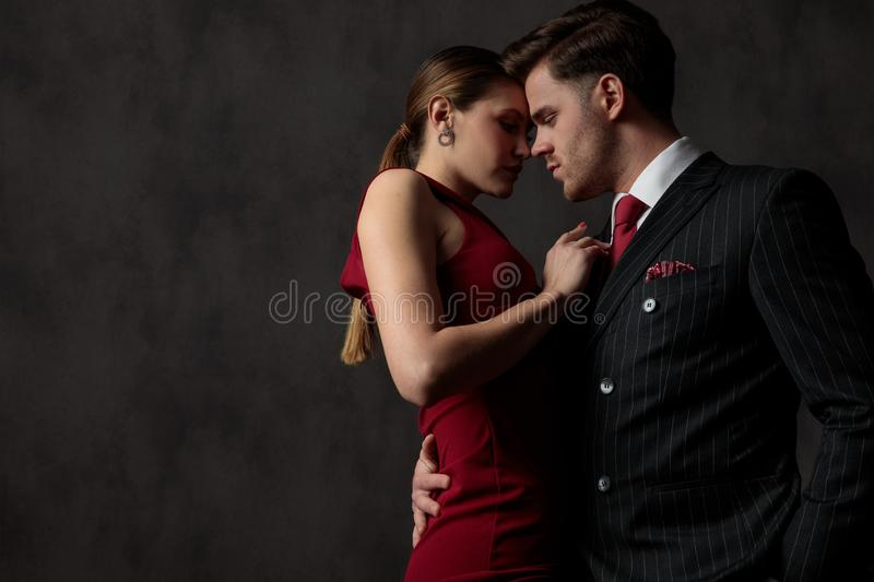 Sexy couple strongly embracing one another and looking with passion. Side view of a young sexy couple strongly embracing one another and looking with passion and royalty free stock photo