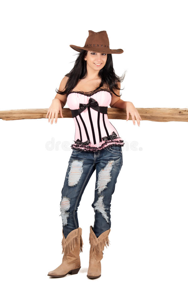 Cowgirl. Pretty cowgirl leaning on a cedar rail, wearing a corset stock photo