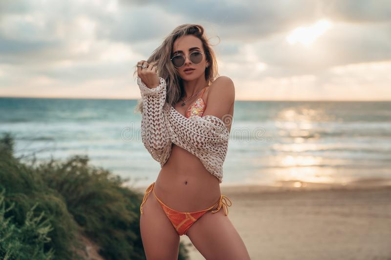 curly-haired blonde model wearing sunglasses, swimsuit and tunic is posing on the beach overlooking the ocean royalty free stock photography