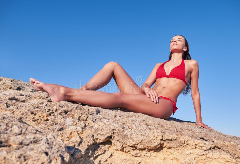 cute young girl in red swimsuit is sitting on stone royalty free stock photo