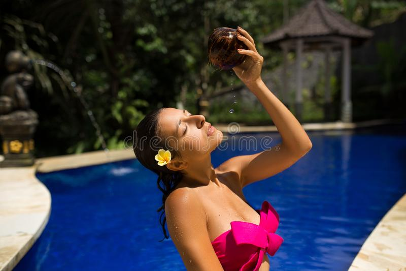 Sexy dünne brunette junge Frau, die mit frischer Kokosmilch im Pool mit blauem Kristallwasser sich wässert Königlicher tropischer lizenzfreies stockfoto