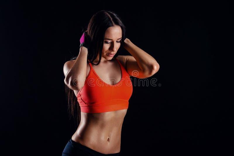 Sexy dünne Frau der schönen Eignung im Activewear, der über schwarzem Hintergrund aufwirft Rückseitige Ansicht lizenzfreies stockbild