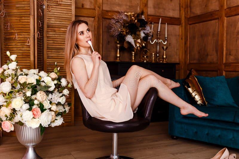 Sexy dünne Frau im beige Kleid sitzt auf einem Stuhl und leckt einen Löffel stockfoto