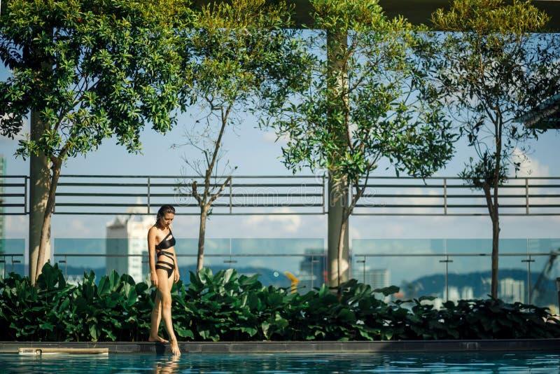 Sexy d?nner kaukasischer Brunette, der zwischen gr?ne B?sche und B?ume auf Rand des Swimmingpools auf Dachspitze mit Stadtbild ge stockfotos