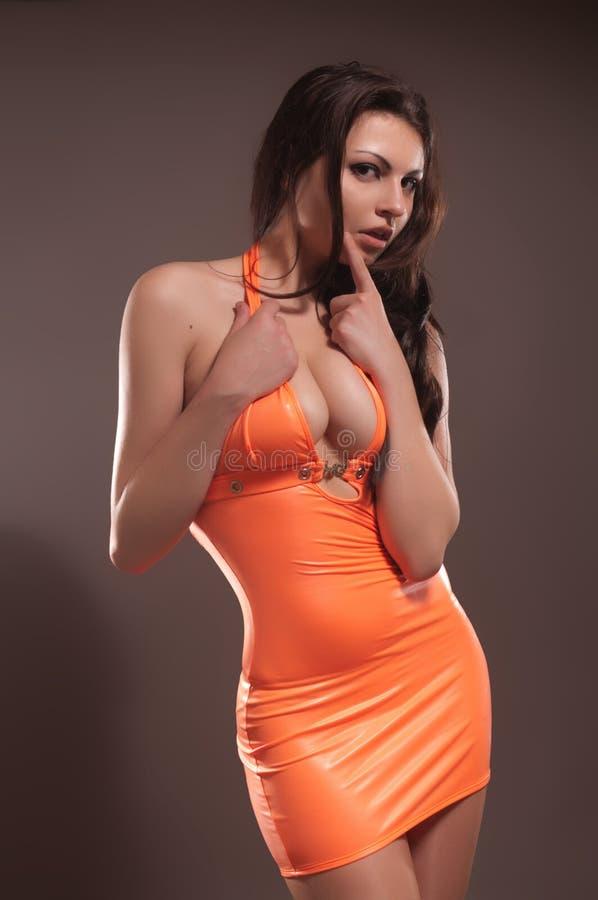 Sexy dame in oranje amuletkleding stock afbeelding